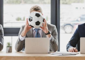 Três homens em um escritório, cada um segura uma bola: basquete, futebol e futebol americano, respectivamente. trade esportivo