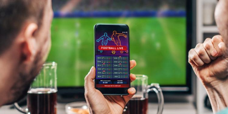 Dois amigos vendo um jogo na TV e analisando suas apostas over e under no celular