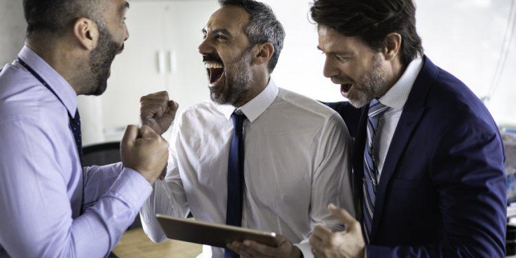 Amigos no escritório comemorando no tablet apostas DNB.