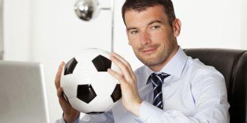 Um homem sentando em seu escritório, de frente para o computador, segurando uma bola de futebol. Como criar um torneio Fantasy