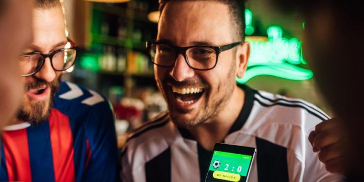 Amigos bebendo cerveja, assistindo jogo de futebol e usando aplicativo móvel para palpites em fantasy