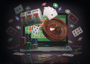 Conceito de casino online. Laptop com roleta, caça-níqueis, fichas de cassino e cartas de jogar isoladas no fundo preto. Ilustração 3D