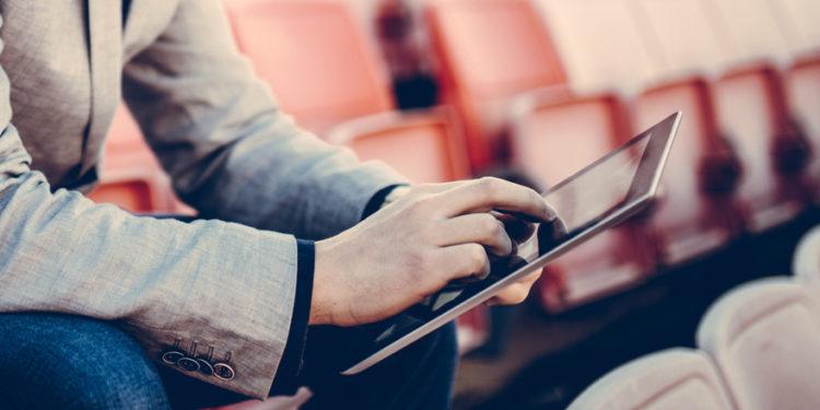 Um homem na arquibancada fazendo prognósticos de futebol em um tablet