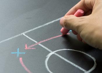 Homem planejando uma estratégia de futebol no quadro-negro. Palpites esportivos
