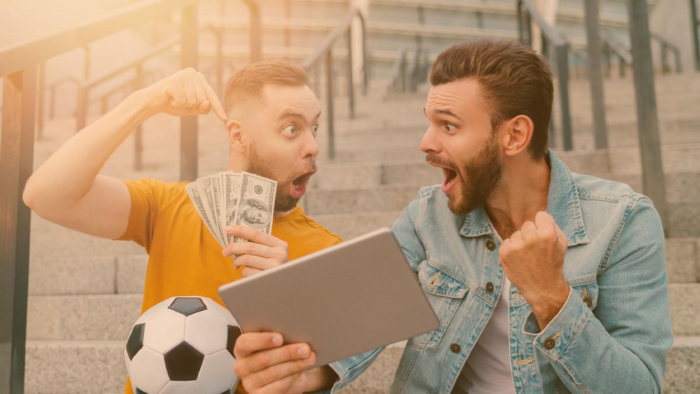 Apostas esportivas: Dois felizes eufóricos jovens barbudos sentados nos degraus do estádio de futebol, assistindo à transmissão ao vivo online no computador tablet, fazendo apostas no time favorito e comemorando a vitória do dinheiro.