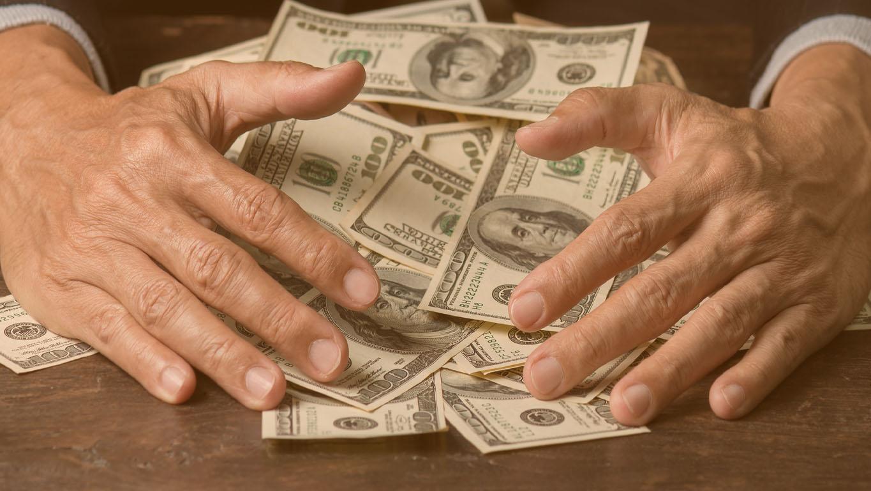 Mãos de homem varrendo dinheiro, conceito de negócio. Homem de sorte, ganhando muito dólar nos jogos de azar, com uma cara sorridente e fundo preto.