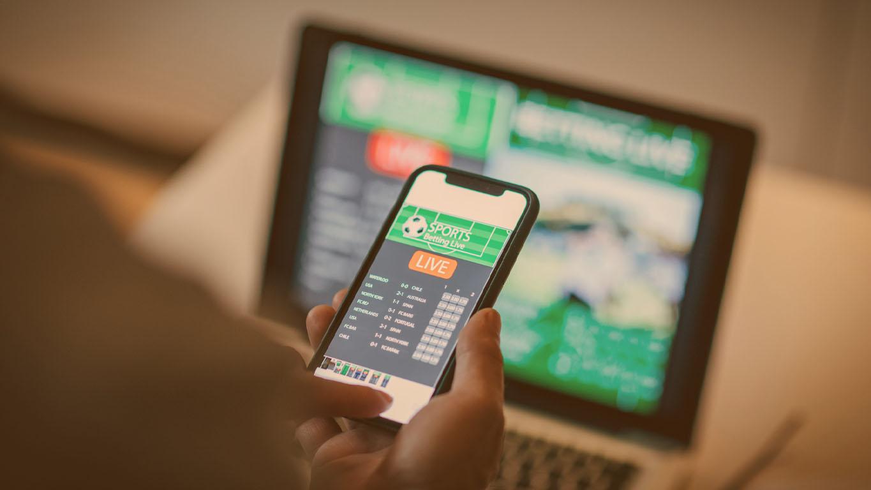 Homem maduro usando aplicativo móvel para apostas ao vivo, jogos de azar online e assistir a uma partida de esportes