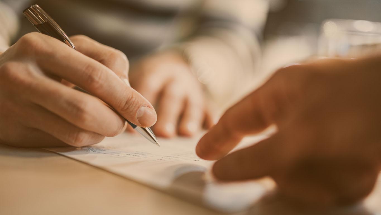 homem assinando um contrato enquanto o consultor está mirando no lugar que ele precisa assinar.