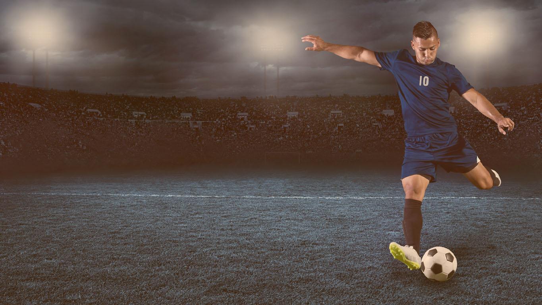 Foto de ação de futebol profissional ou jogador de futebol durante o jogo em um estádio totalmente iluminado à noite
