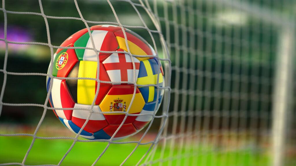 bola de futebol com desenho das bandeiras de alguns países na rede do gol