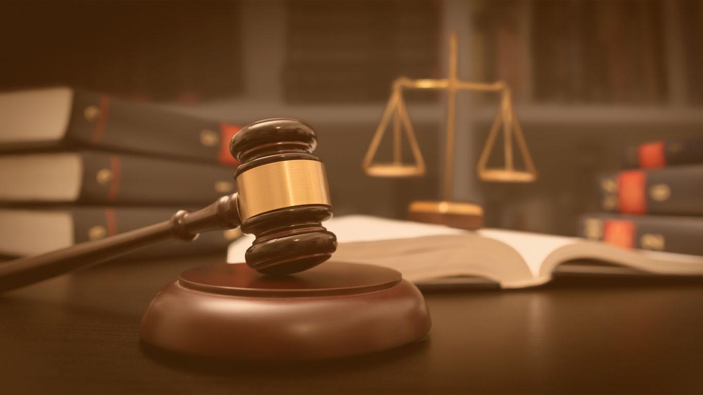 Fair play financeiro: Martelo e escala do juiz no tribunal. Biblioteca com muitos livros no fundo