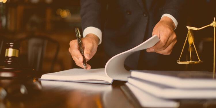 Fair play financeiro: Advogado assinando contrato ao lado de uma balança da justiça em miniatura