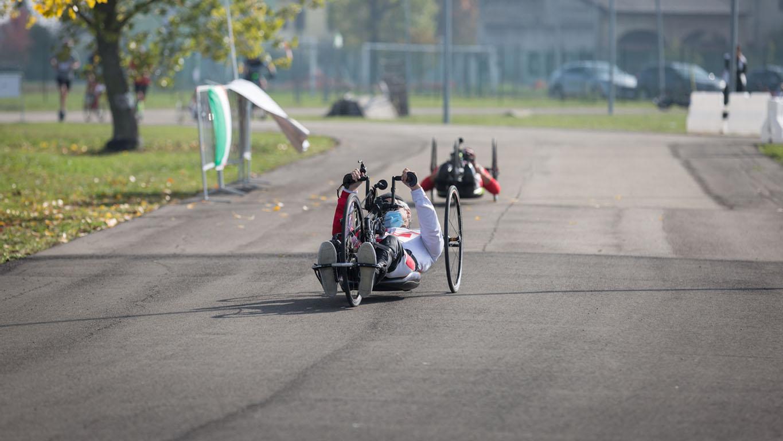 casal de atleta com deficiência treinando com suas bicicletas de mão em uma pista.