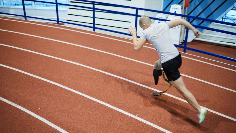 Paralimpíadas: Corredor paraolímpico ativo com perna deficiente movendo-se rapidamente na linha da pista no estádio durante a competição