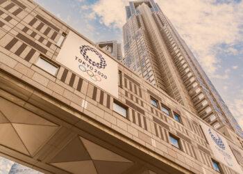 Paralimpíadas: Tóquio, Japão - 29 de novembro de 2017: 2020 conceito olímpico - olhando a vista do edifício do governo metropolitano de Tóquio com o logotipo dos Jogos Olímpicos de Tóquio 2020, os arranha-céus refletem o dramático céu azul