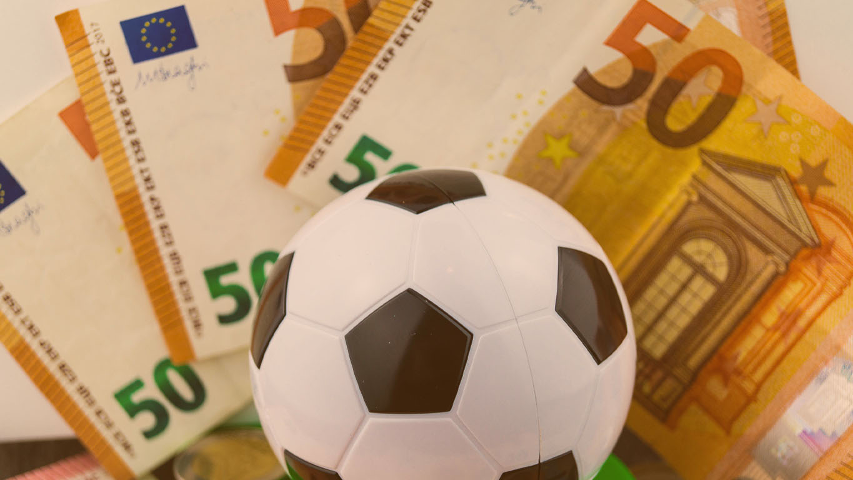 imagem com uma bola na frente de algumas notas de euro