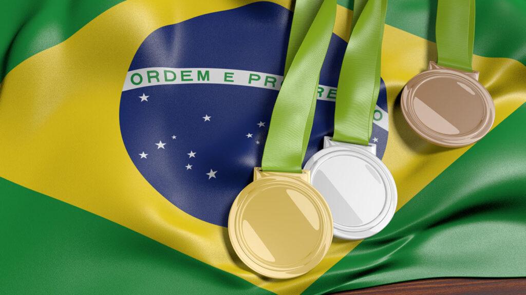 Renderização 3D das medalhas de ouro, prata e bronze sobre a bandeira do Brasil para os jogos de 2016.