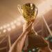 Times com mais títulos no Brasil: Atleta segurando a taça do troféu acima da cabeça no estádio