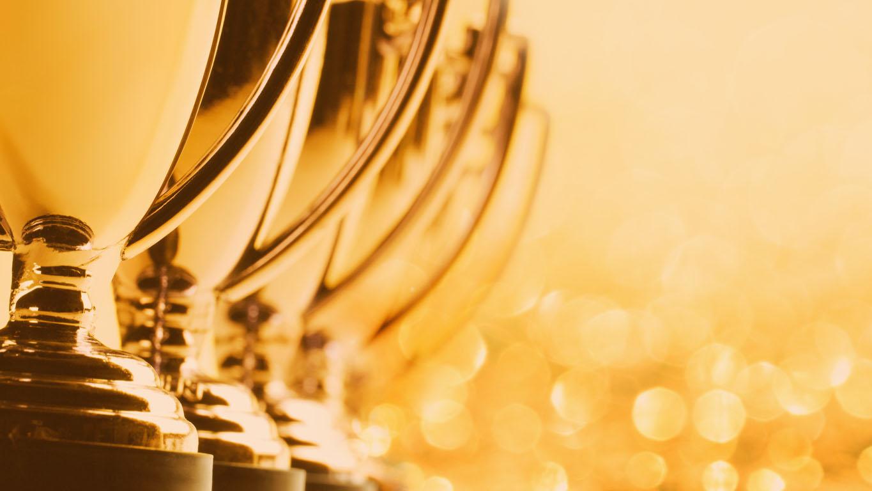 Uma fileira de troféus cortados em uma panorâmica fotografada com uma profundidade de campo muito rasa em um fundo de glitter e luzes desfocadas.