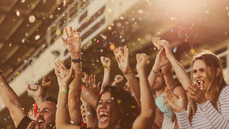 Fãs de esportes batendo palmas em carrinhos com confetes caindo. Torcedores do time de futebol torcendo no estádio.