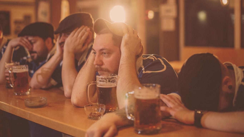 Grupo de pessoas em um bar, homens desesperados assistindo a um jogo de esportes juntos em um bar.