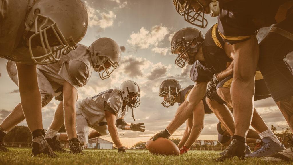 Regras do futebol americano: Jogadores no centro do campo, prontos para iniciar a partida
