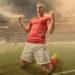 maiores artilheiros da Libertadores: Jogador profissional de futebol masculino, vestido com camisa vermelha, meias e shorts brancos, ajoelhado com os braços erguidos e os punhos cerrados, gritando em comemoração por ter acabado de marcar um gol. O jogador de futebol está em um campo ao ar livre, com outros companheiros de chá e jogadores rivais em um estádio de futebol genérico cheio de espectadores.