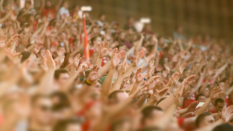 Multidão batendo palmas no pódio do estádio