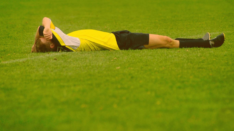 Os maiores recordes do futebol brasileiro: jogador de futebol deitado na grama após um jogo perdido