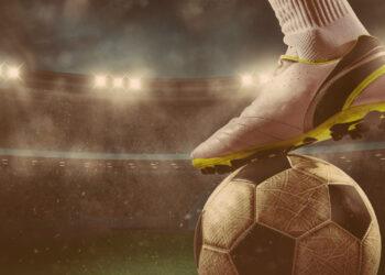 Os maiores recordes do futebol Brasileiro: Cena de futebol à noite partida com jogador pronto para atirar a bola