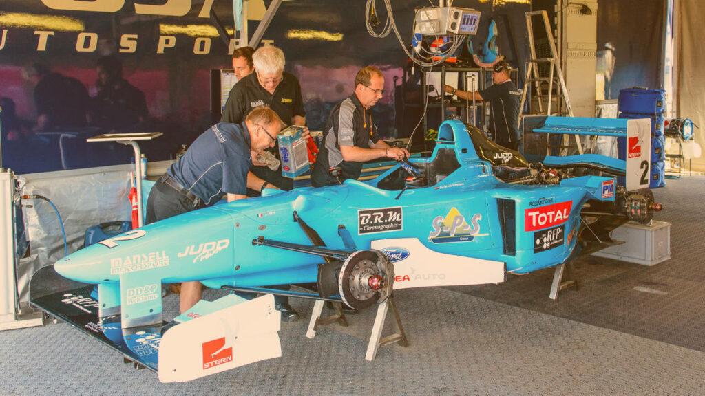 Novas regras da fórmula 1: Zandvoort, Holanda - 7 de julho de 2013: 1997 Benetton B197 - carro de F1 (Jean Alesi) no paddock da pista de corrida de Zandvoort durante o Masters of F3 de 2013. Os mecânicos estão trabalhando no carro.