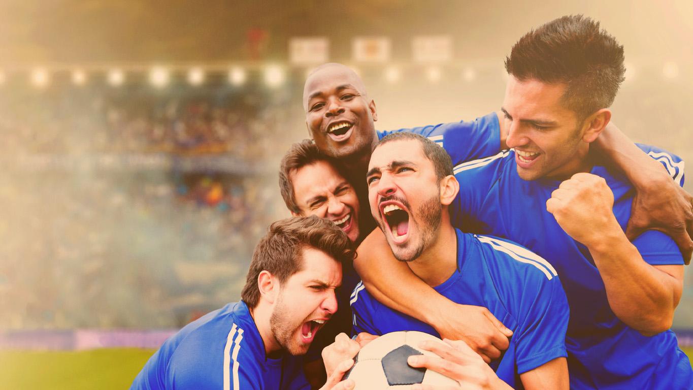 Equipe de futebol feliz comemorando um gol no estádio