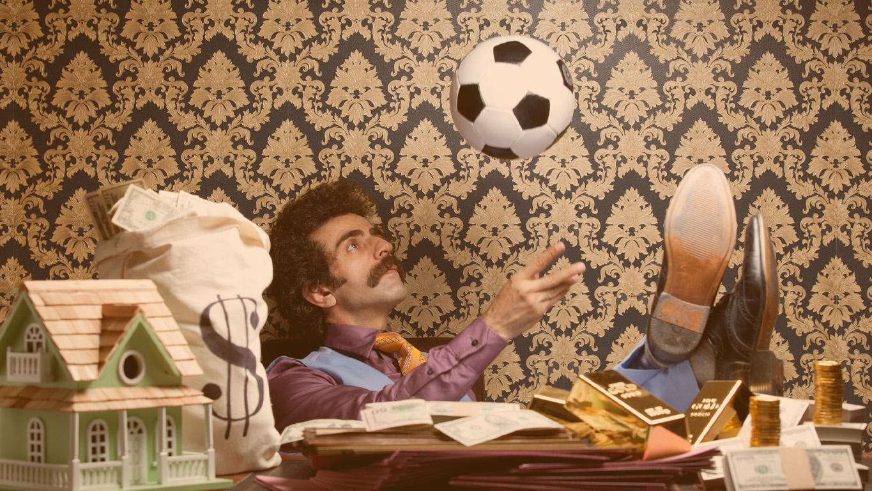 Homem adulto sentado na mesa e brincando com uma bola de futebol. Uma casa modelo, bolsa de dinheiro, notas de dólar e alguns lingotes de ouro são colocados na mesa. Ele está jogando uma bola na cabeça. Ele está vestindo uma camisa roxa e cintura azul. Ele tem bigode e cabelo comprido. Ele tem as pernas na mesa. O fundo de papel de parede é usado para aparência antiquada.